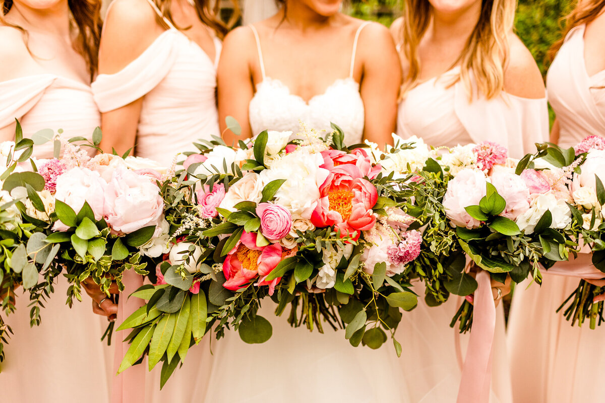 Bride and bridesmaids in blush with coral bouquets at stonebridge country club