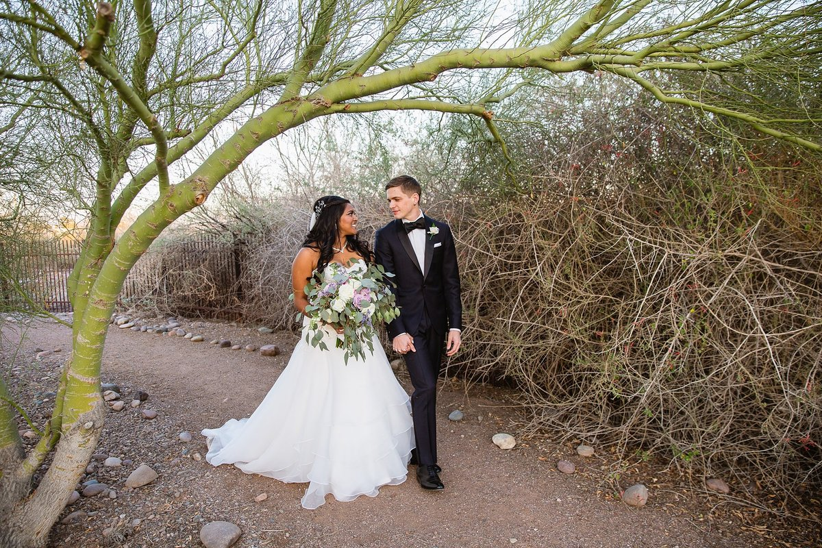Bride and groom walking together at their desert wedding by Phoenix wedding photographer PMA Photography.