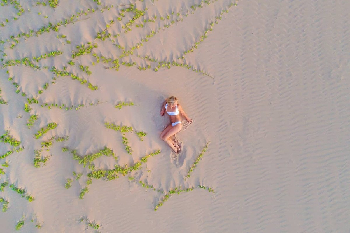 Drone portrait on Maui of woman in swimwear lounging on textured sand