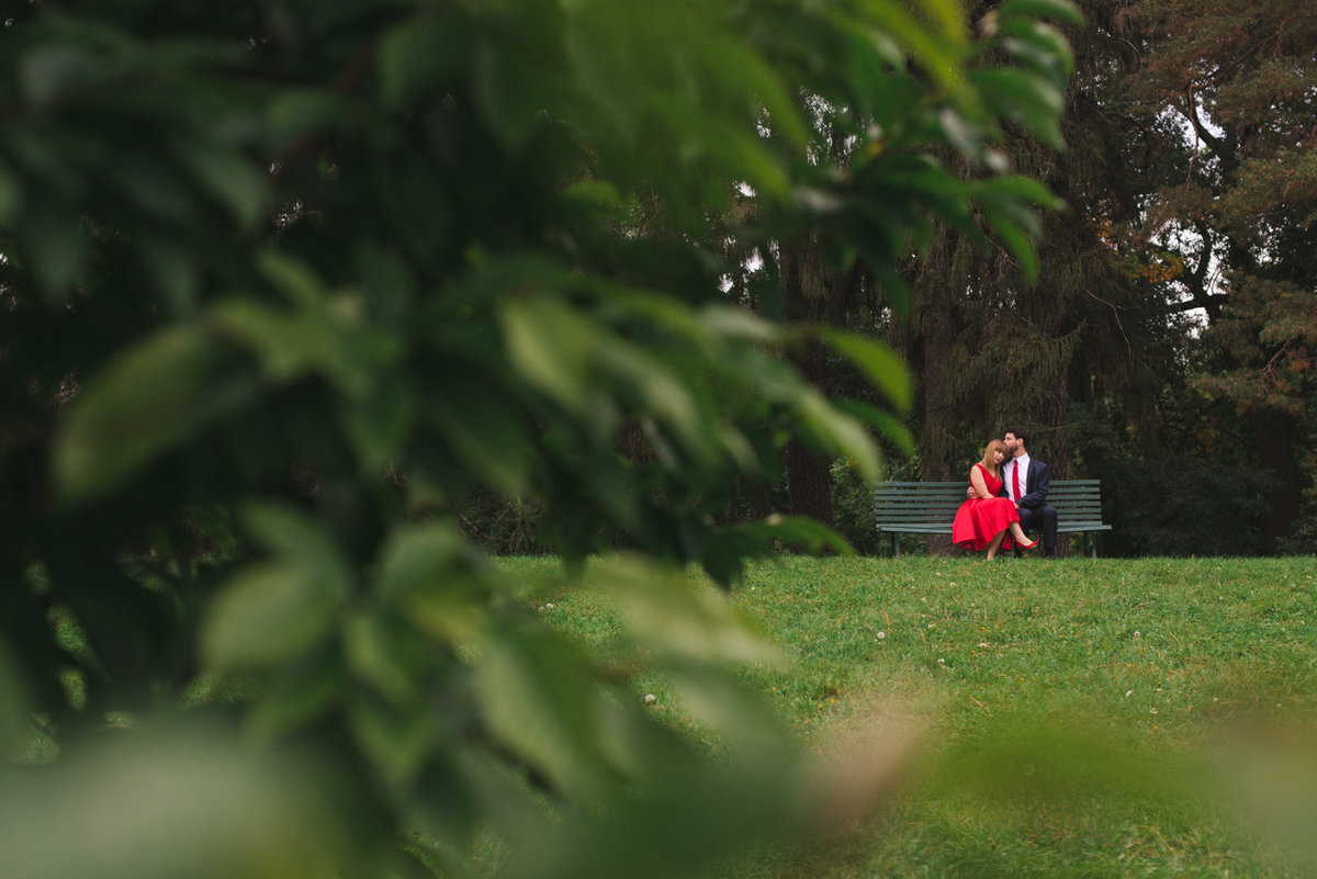 Girl wearing red dress sitting on a bench with her fiancee among the trees