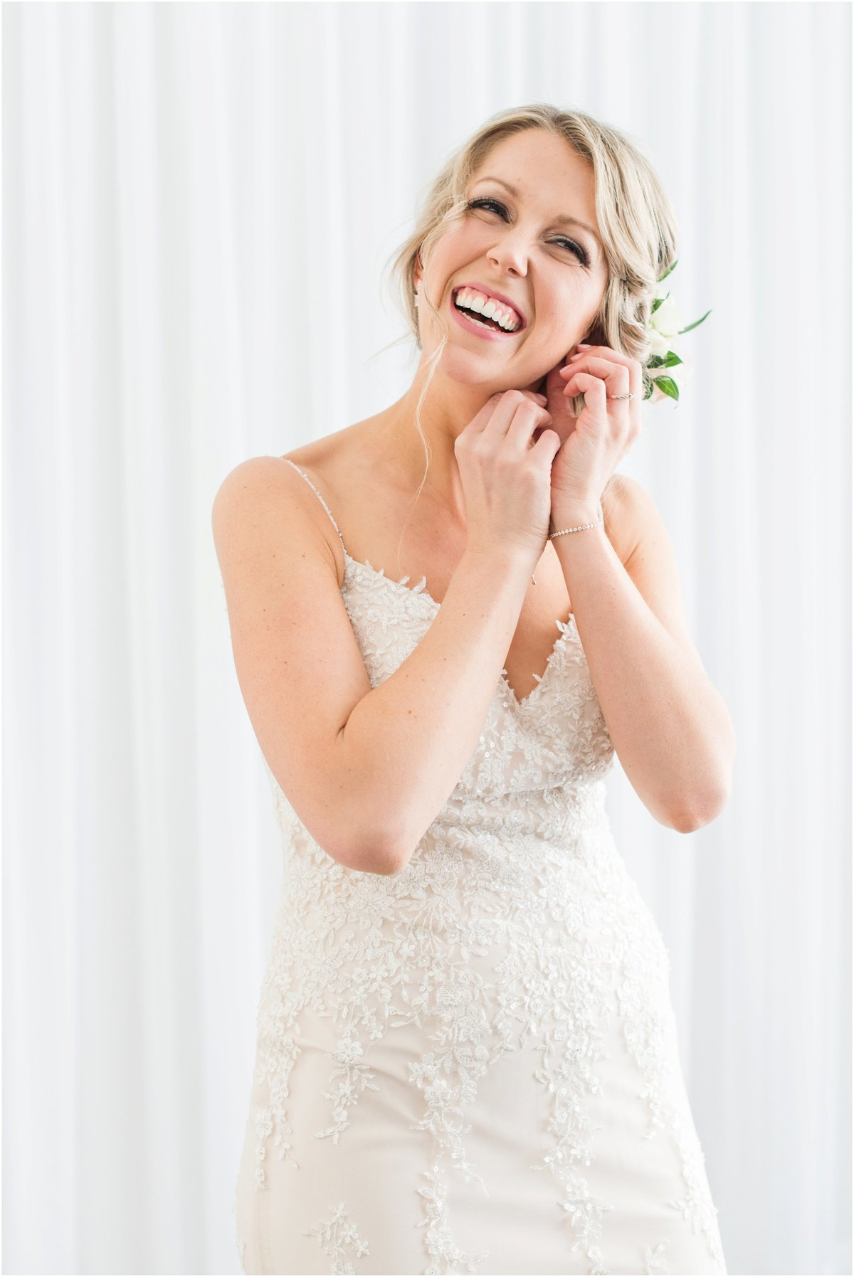 Bride putting on earring laughing