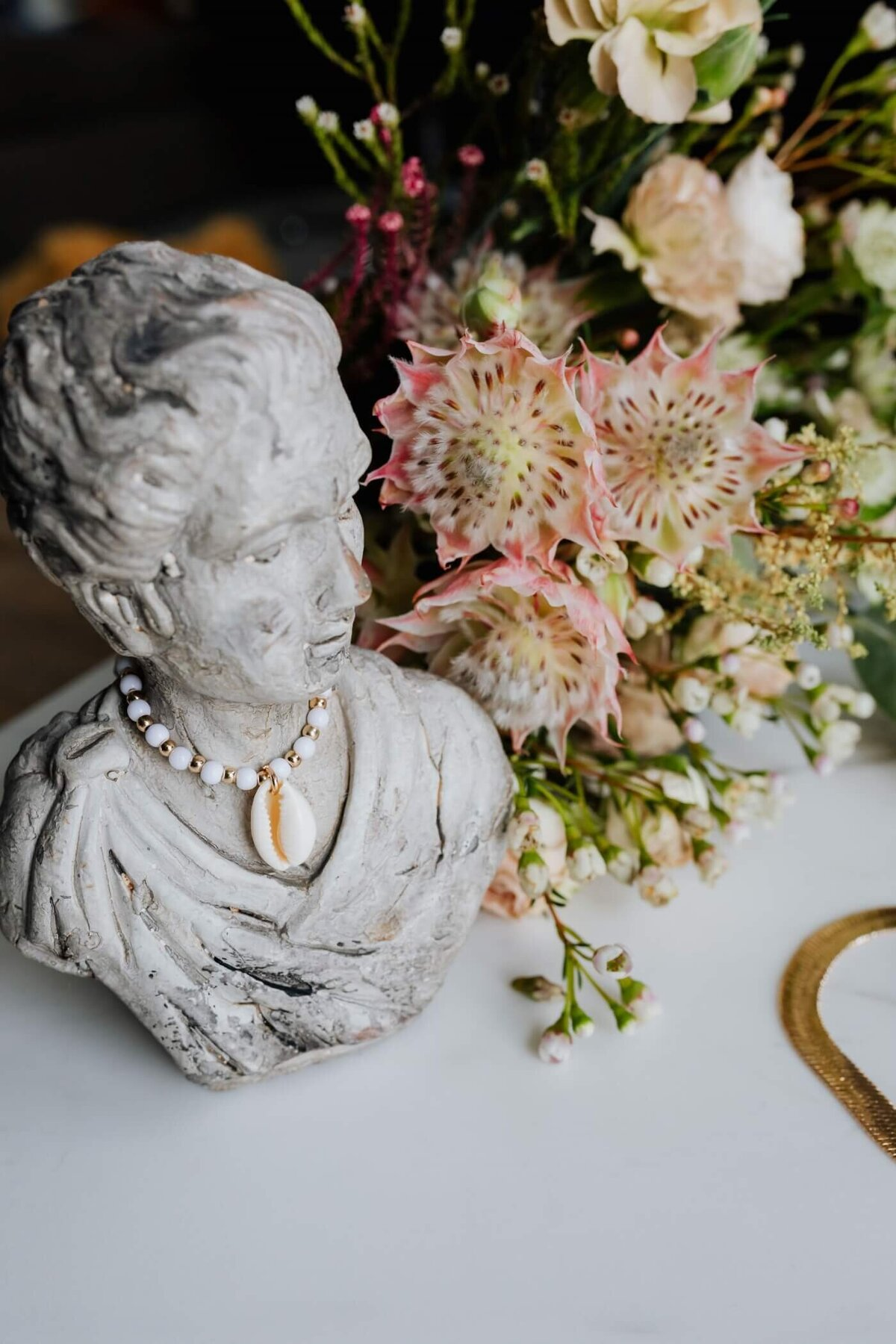 Grey Stone Bust of Woman as a display for Necklace with Bouquet