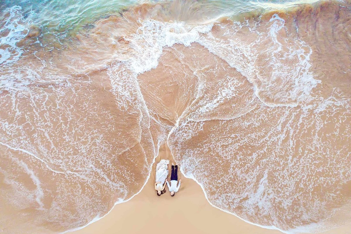 Bride and groom in wedding attire photographed by drone in Hawaii on the beach