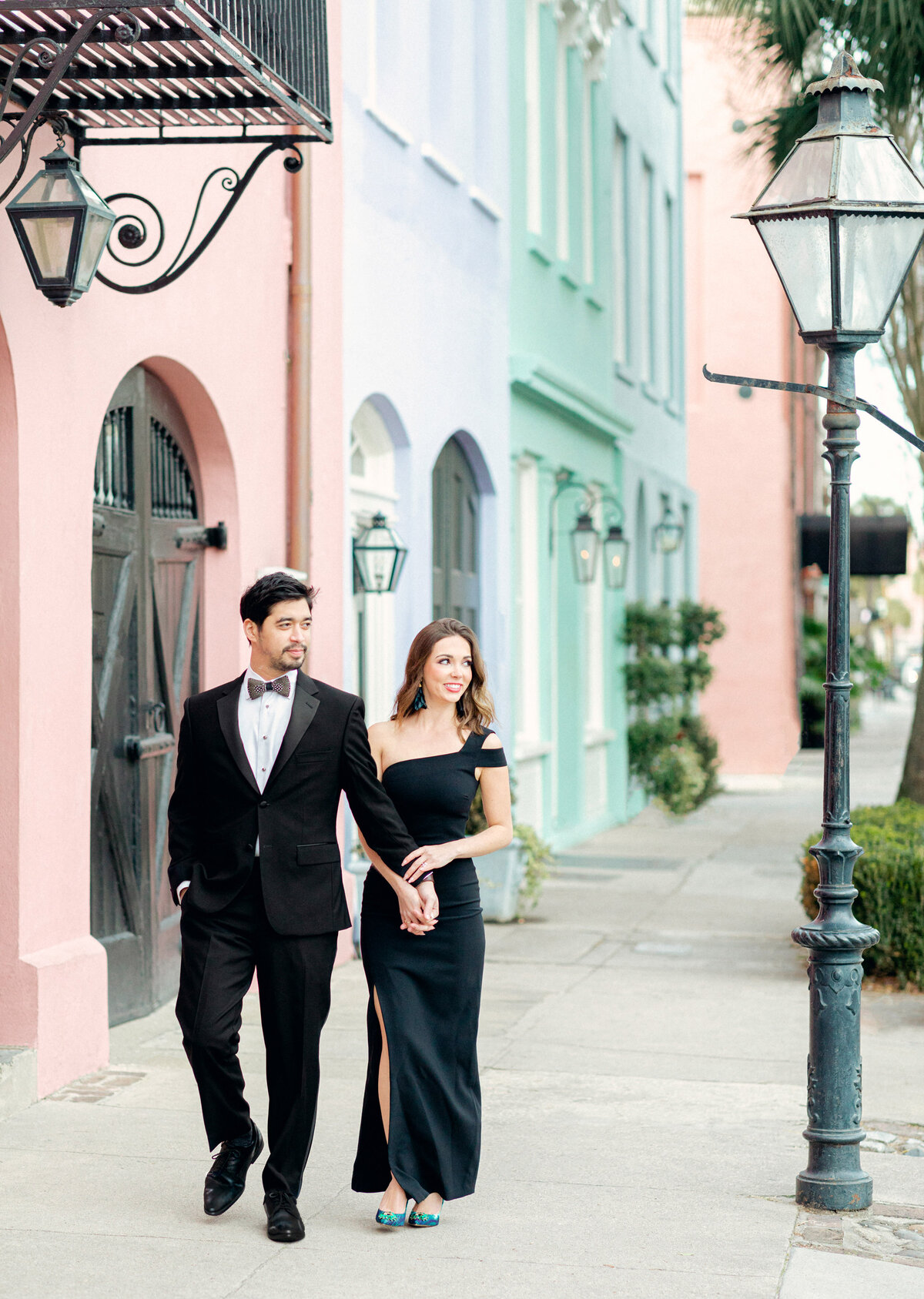 Man in tuxedo and girl in black dress walking by rainbow row homes