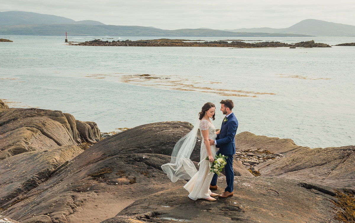 Bride with black hair, holding a white bouquet and wearing a vintage, sequenced dress with groom in blue suit standing on rocks overlooking the Atlantic ocean