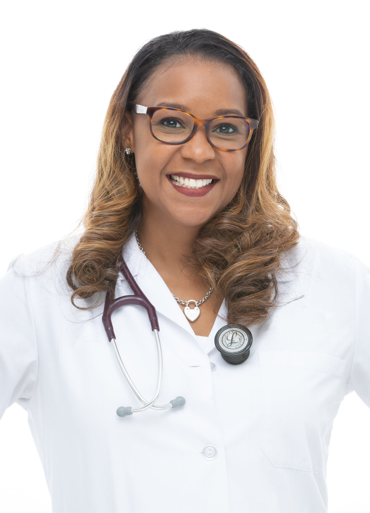 An African American woman doctor with glasses poses for a headshot on white background at Janel Lee Photography studios in Cincinnati