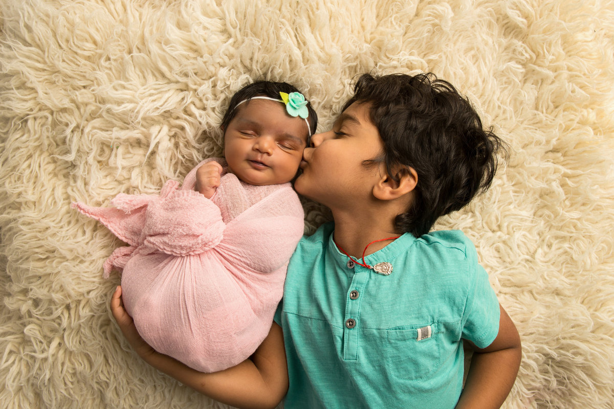 A big brother loves on his baby sister during their portraits in our Baltimore studio