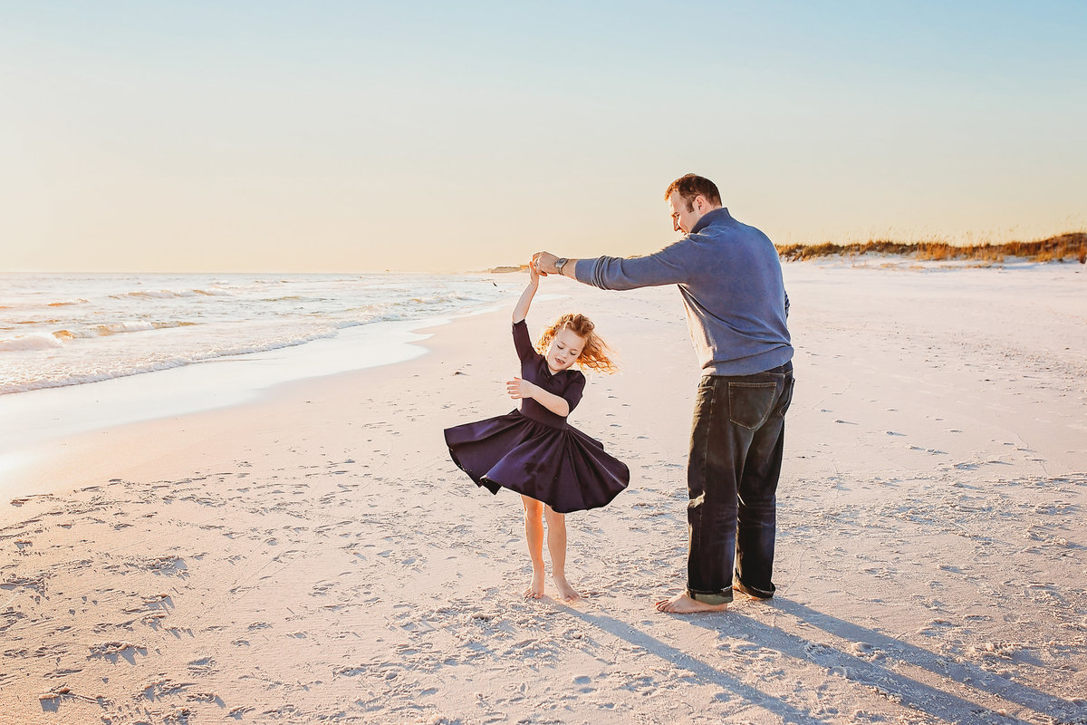 Dad dancing with young daughter, twirling, on beach