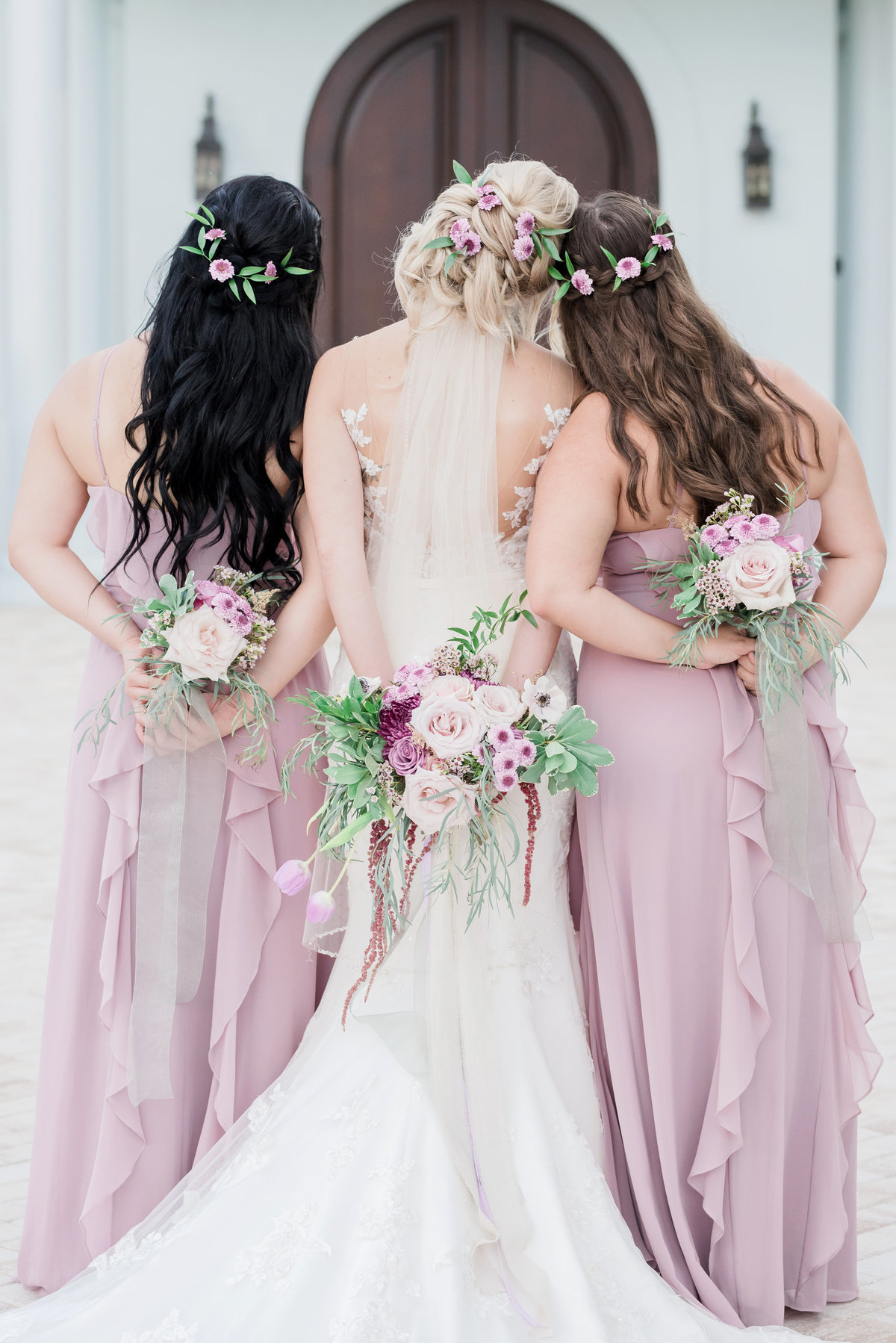 Bride and her two bridesmaids in lavender link arms with their bouquets behind their backs
