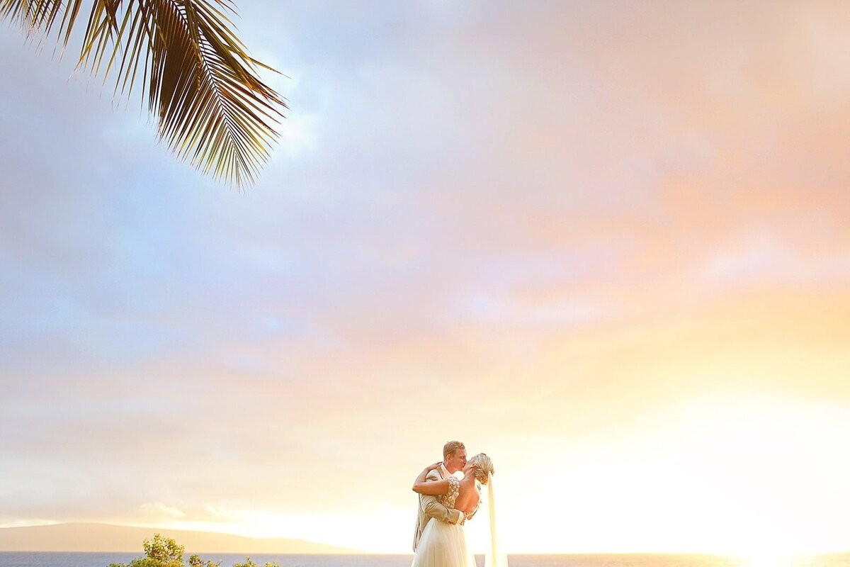 Palm tree frames shot of bride and groom kissing after their wedding on Maui