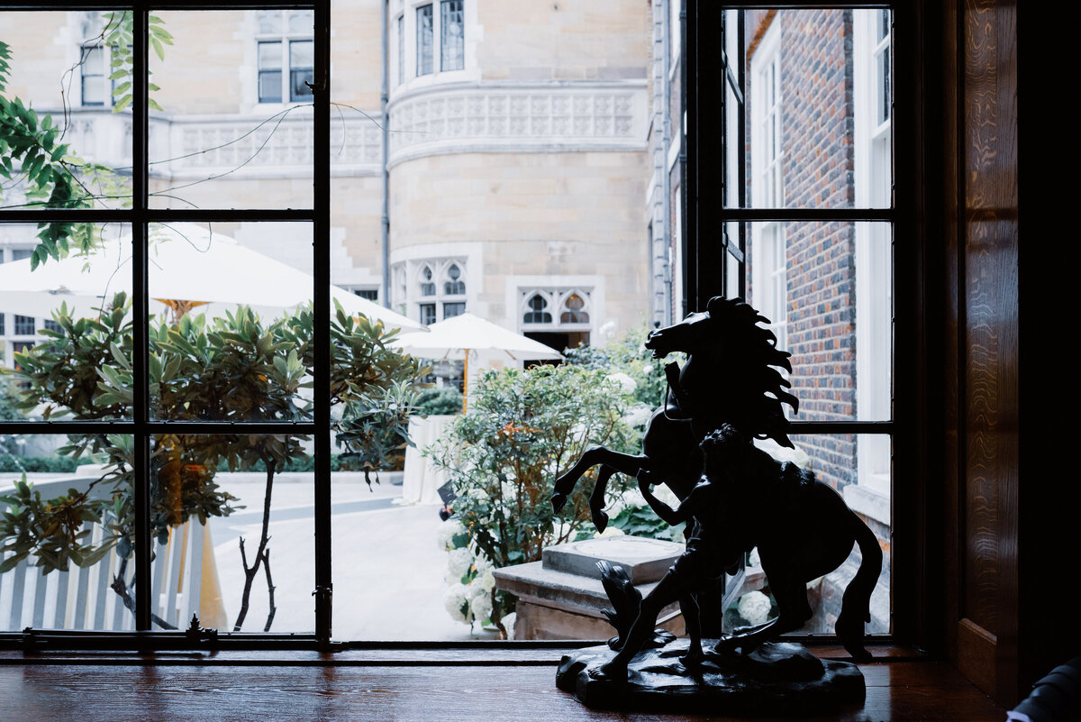 A rearing horse sculpture by a metal framed window overlooking a courtyard at a luxury london wedding.