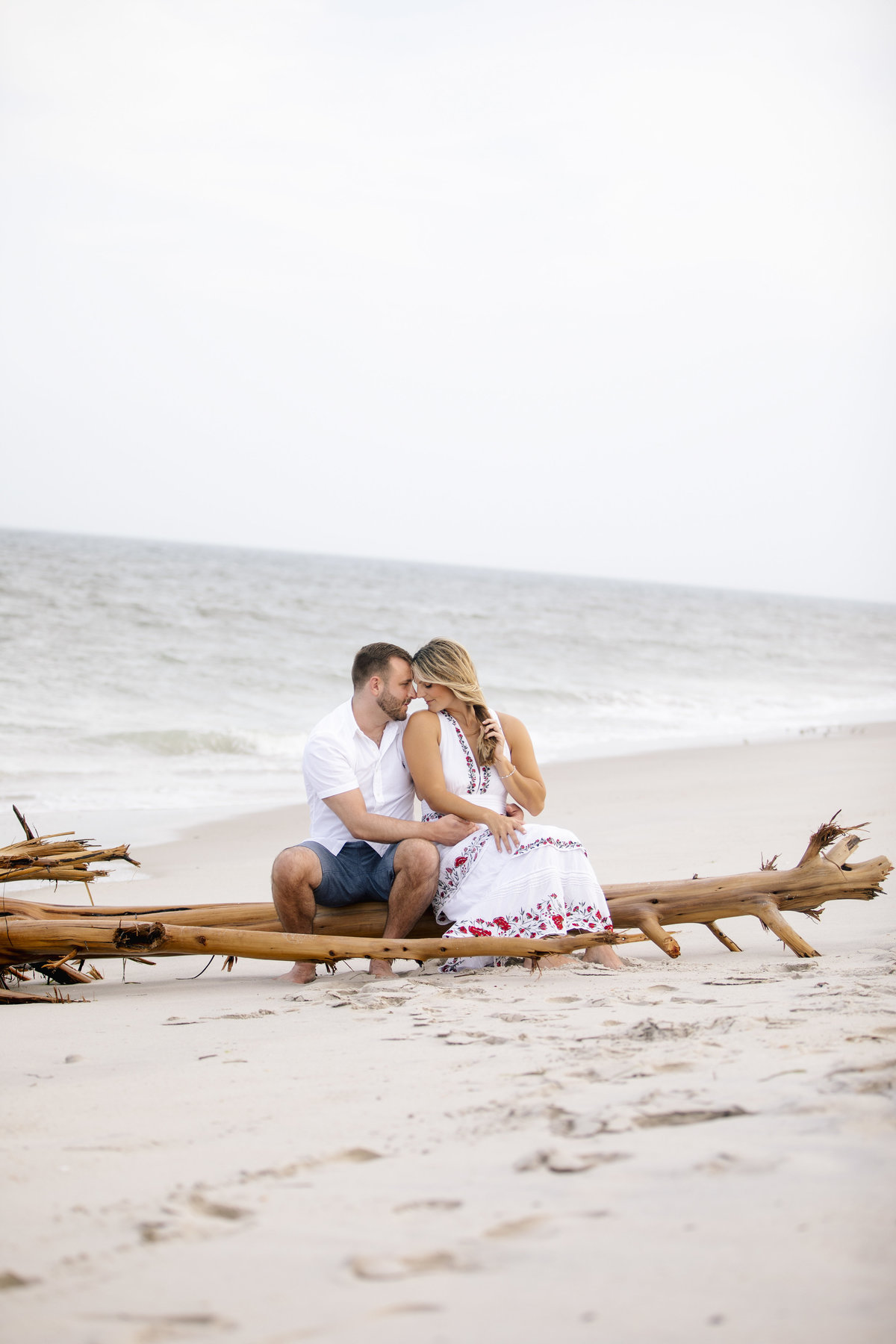 engaged couple sit on beach on driftwood  at LBi session