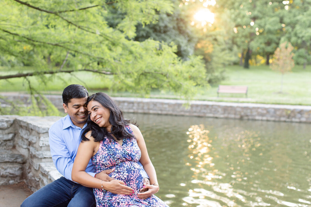 Spring Sunset Maternity Session with maxi dress sitting by fountain  at Oak Knoll Park in St. Louis by Amy Britton Photography Photographer  in St. Louis
