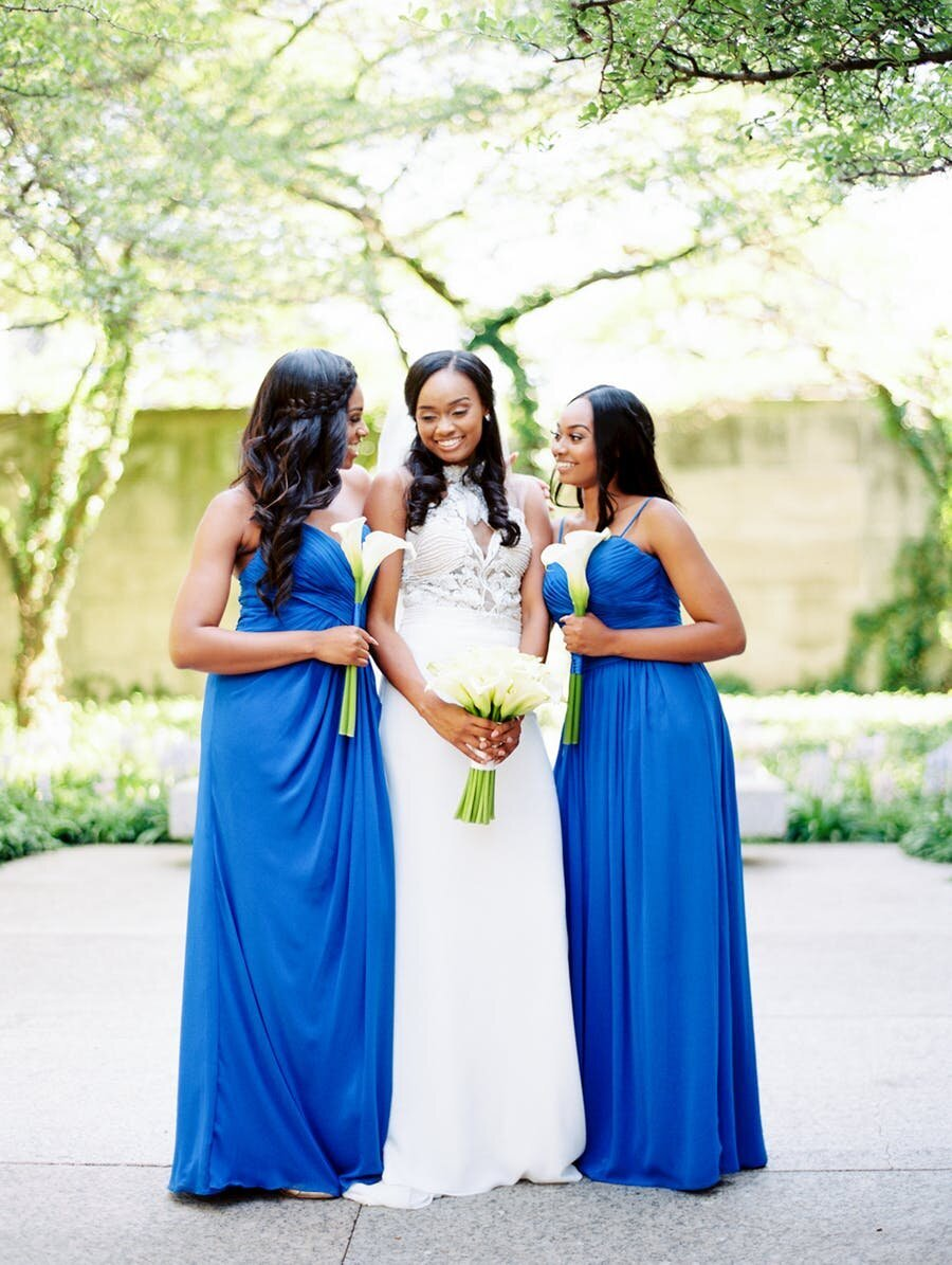 Bride smiling with her sister's in blue dresses