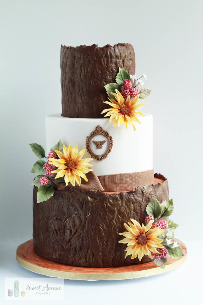 woodland tree bark wedding cake with sunflowers and sugar berries