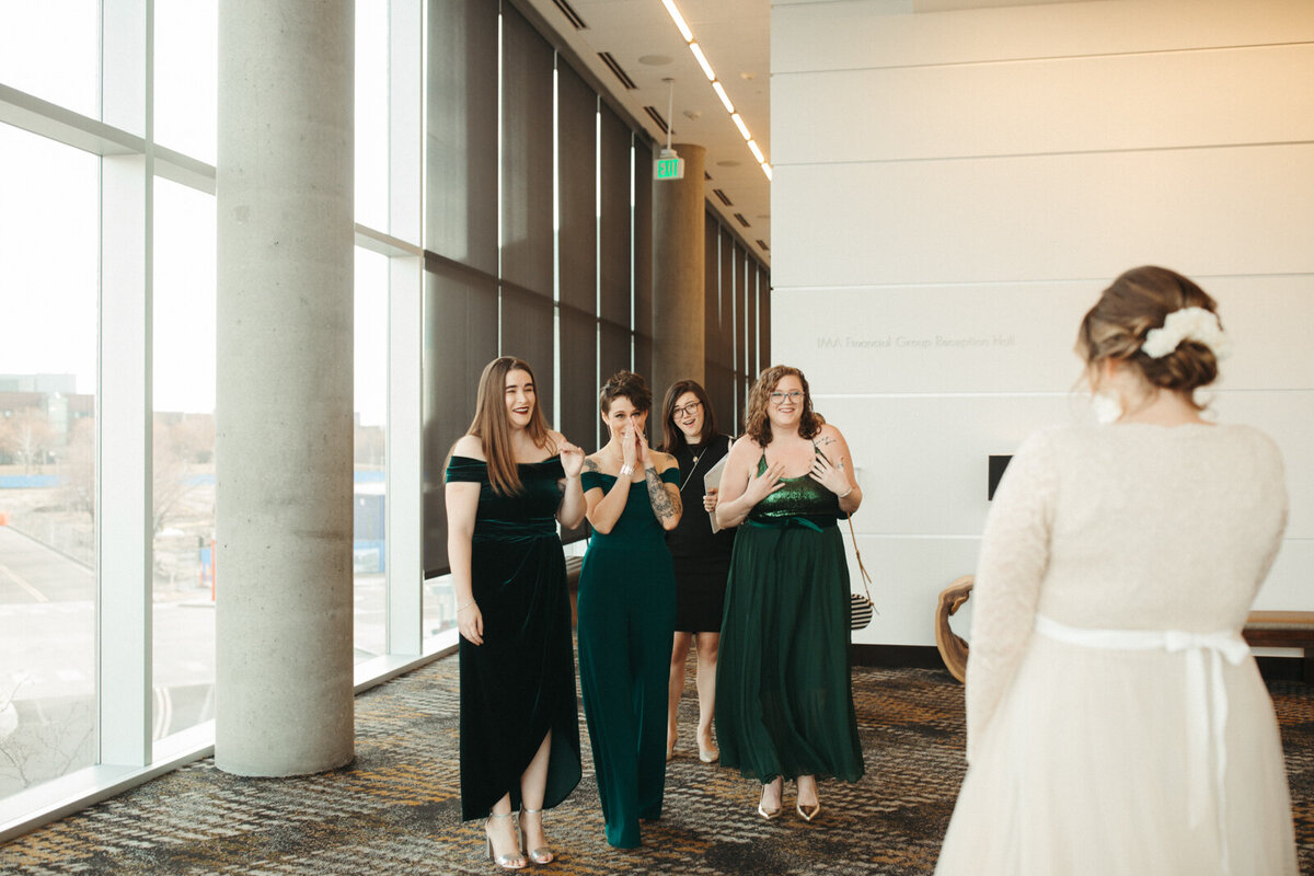 Four bridesmaids wearing green look happy and emotional at seeing the bride for the first time, who is shot from behind.