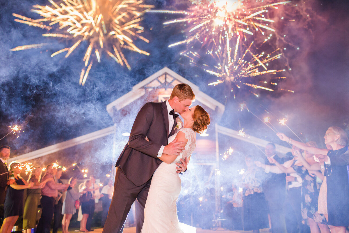bride and groom kissing under fireworks at 9 oaks farm