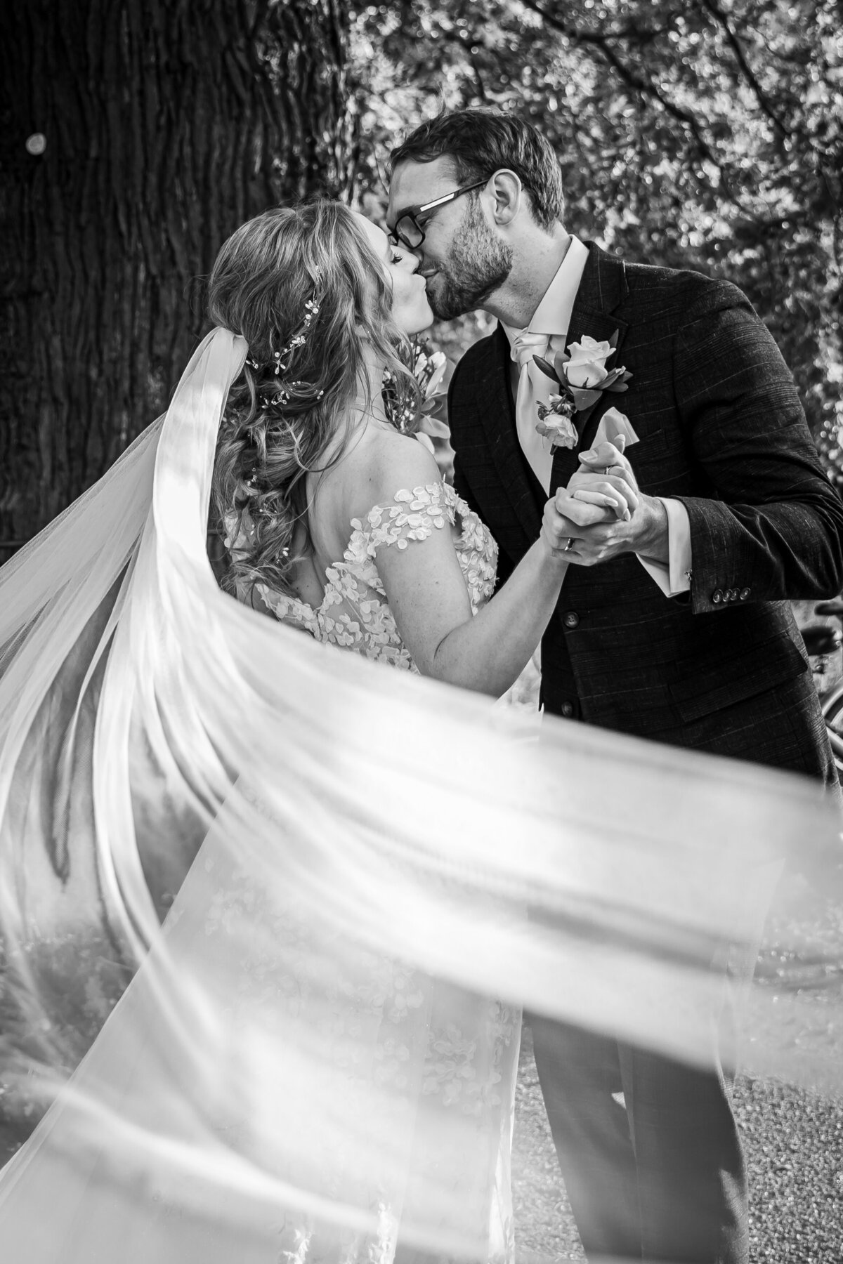 A bride and groom kissing with her veil blowing in the wind