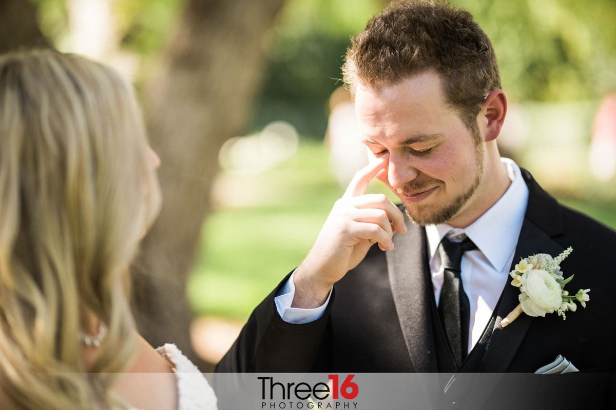 Groom wipes away his tear as he stands in front of his Bride at the altar