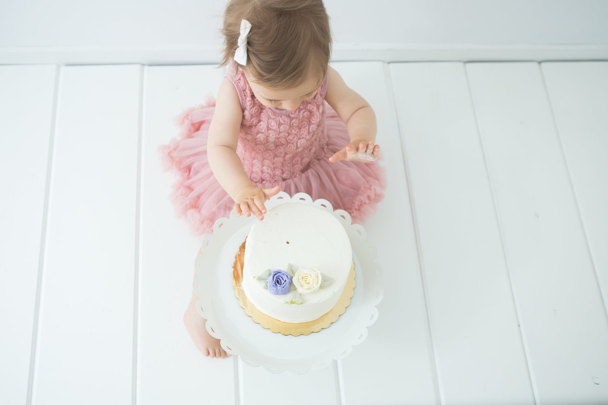 bird's eye view of baby girl smashing birthday cake {Milton Baby Photographer}