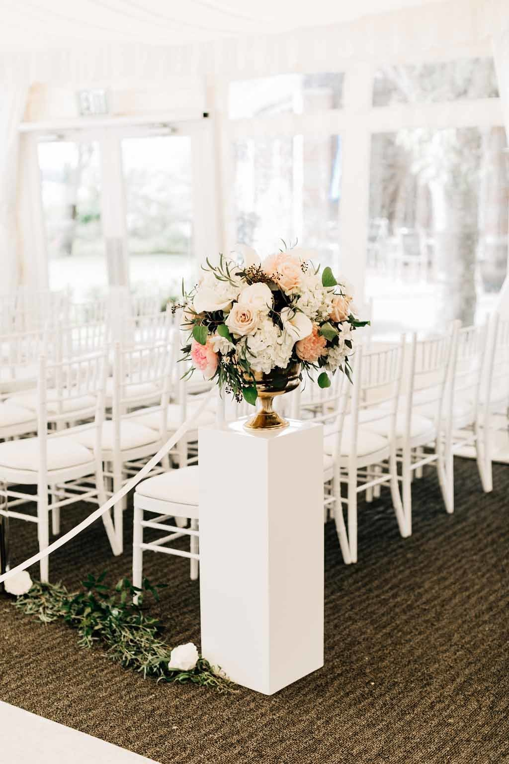 Gold urn blush and cream floral on stone pillars  stand on either side of aisle entrance.