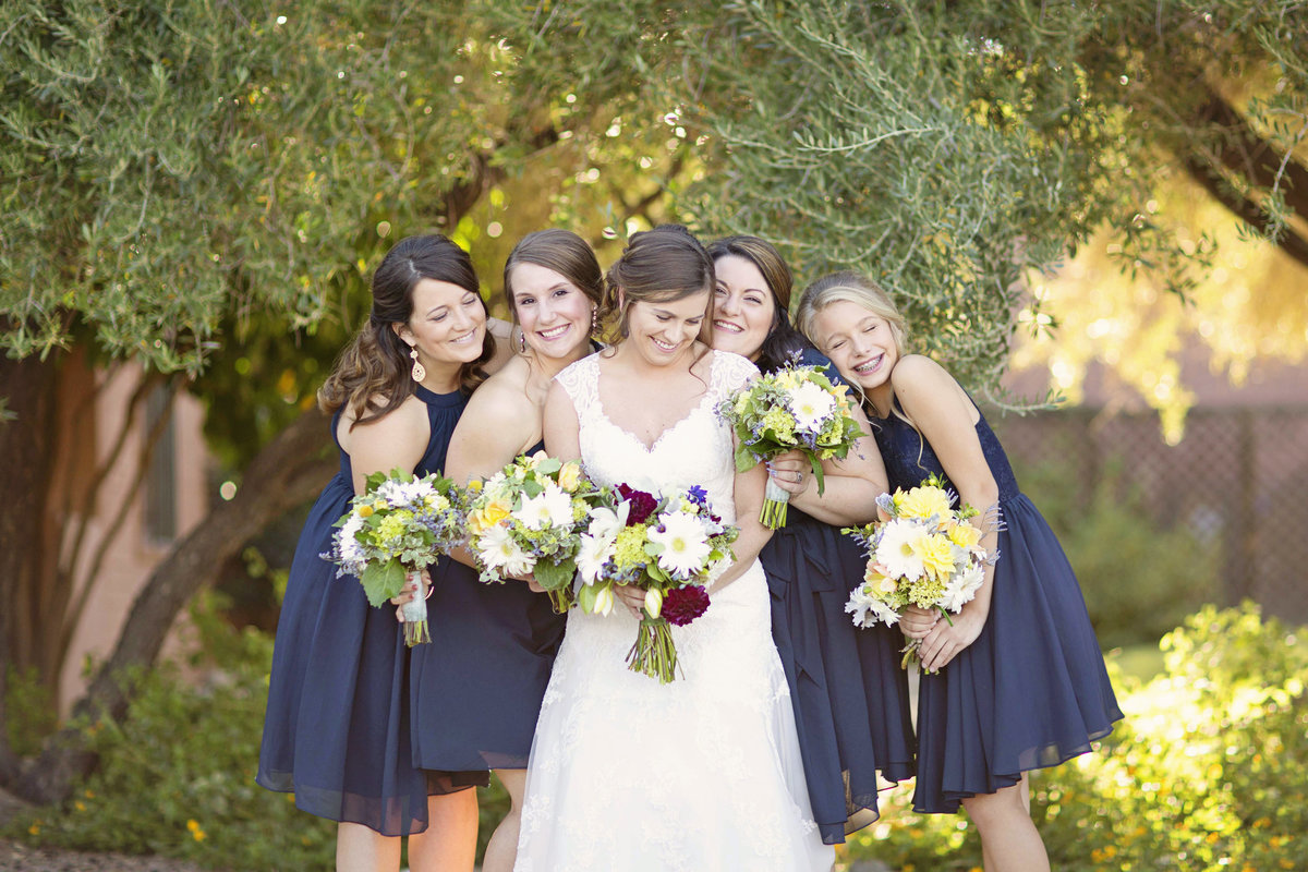 Bridesmaids in navy dresses laugh around bride at the Mountain Oyster Club in Tucson, AZ