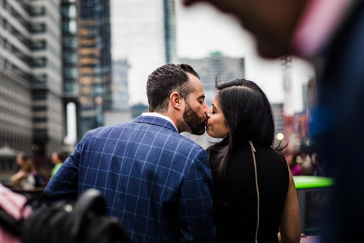 A couple kisses each other on a bridge during a downtown Chicago engagement session.