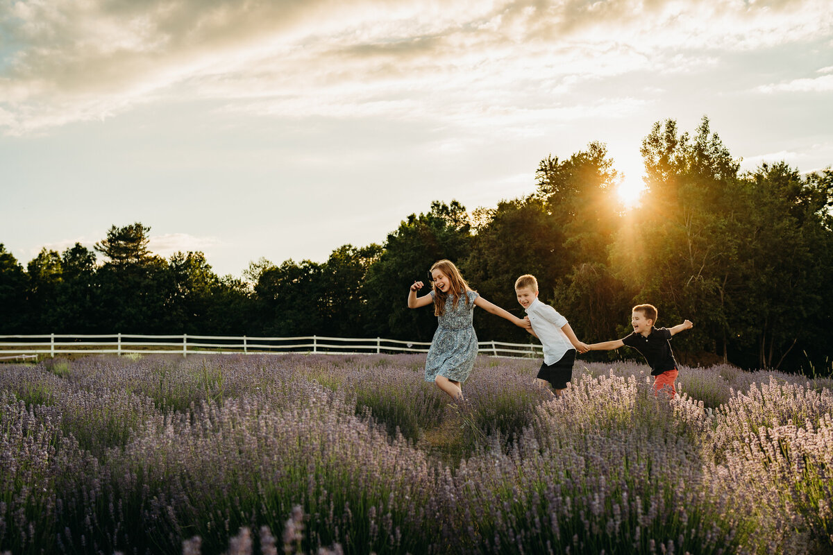 three siblings hold hands and run through lavender field at sunset
