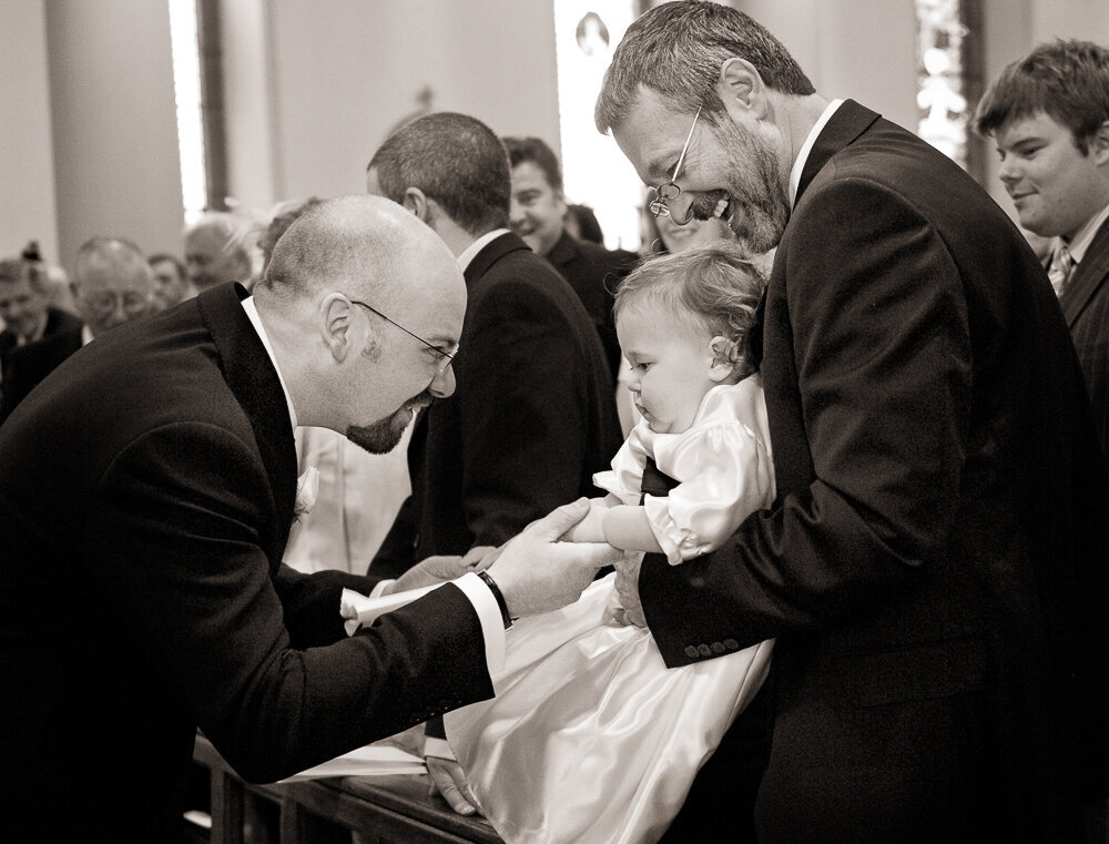 Baby flower girl in satin dress shaking hand with a groom, wearing black in the church