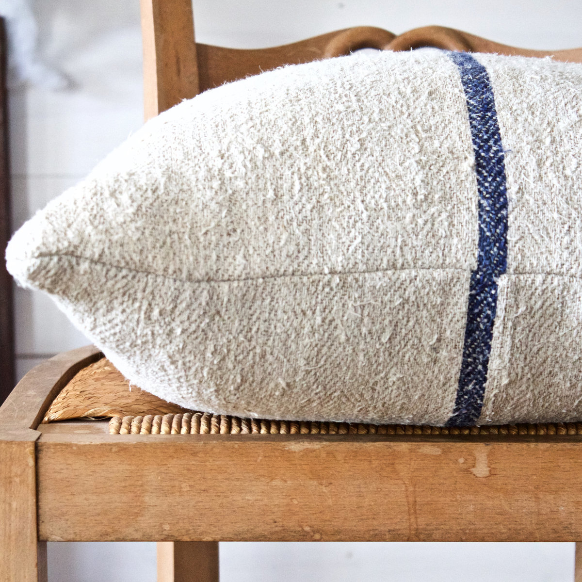 detail of cream grain sack pillow with a blue stripe sitting on a chair