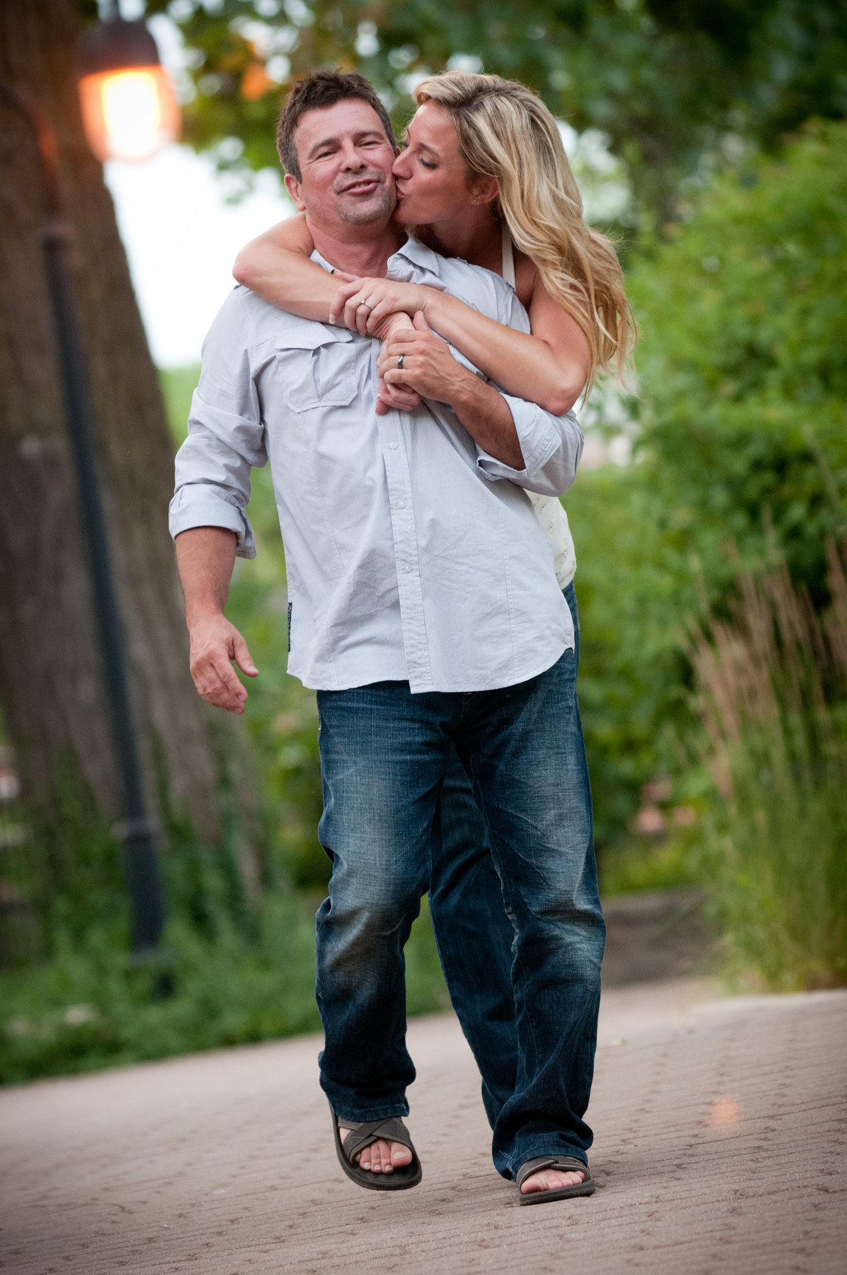 Engagement couple playfully walk along the Naperville River Walk