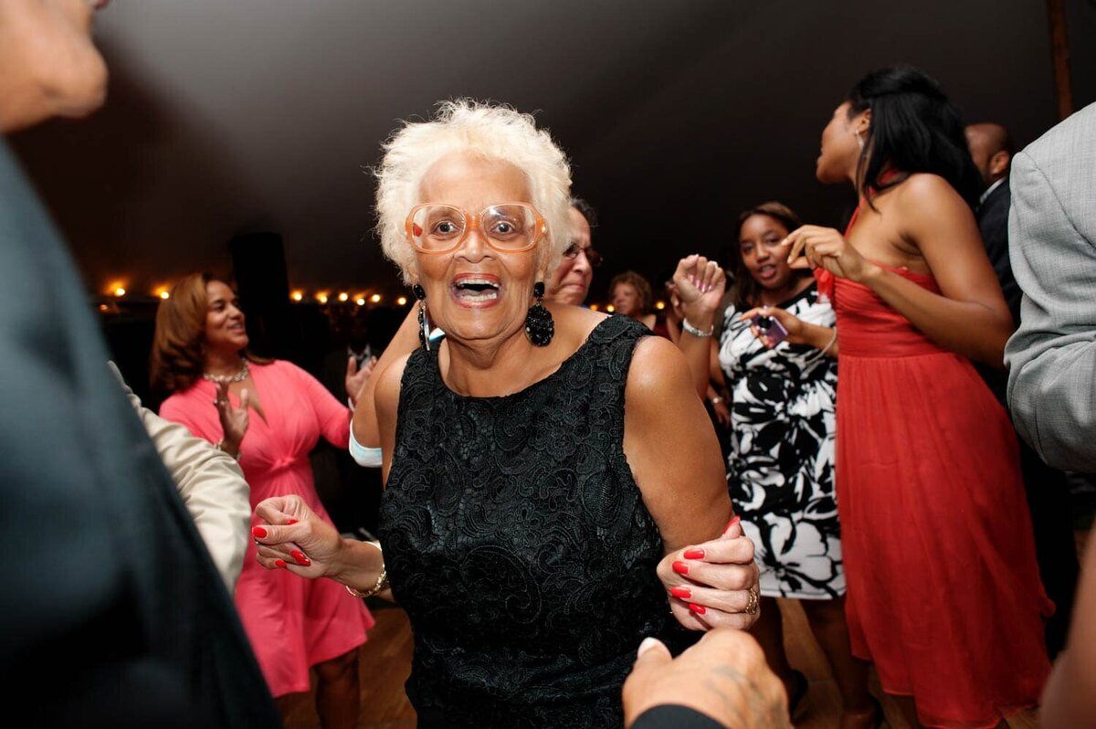 a grandma in fun orange glasses dances and laughs during the wedding reception