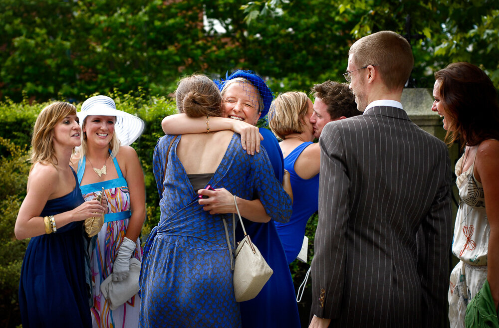 happy wedding guests in blue hugging in a church yard surrounded by friends