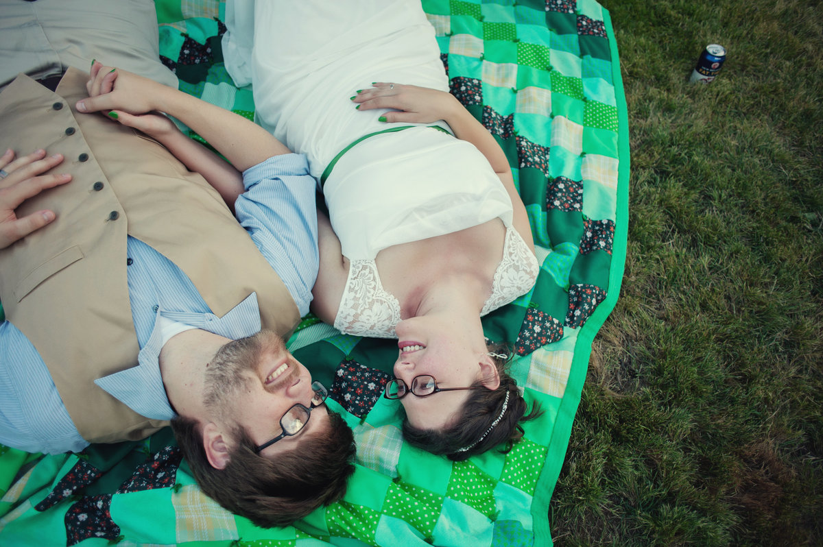 bride and groom lay on colorful green quilt