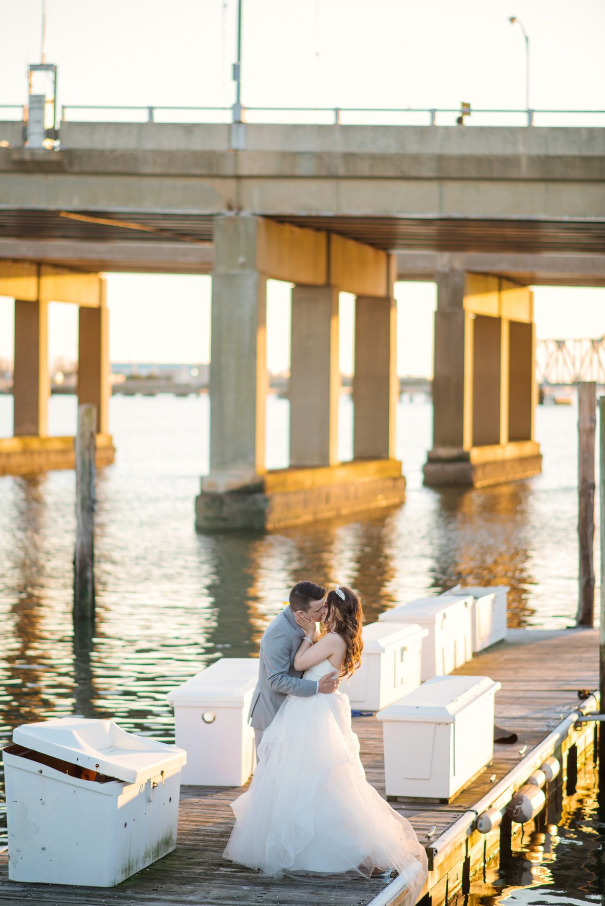 bride and groom kissing photo near water at bridgeview yacht club wedding