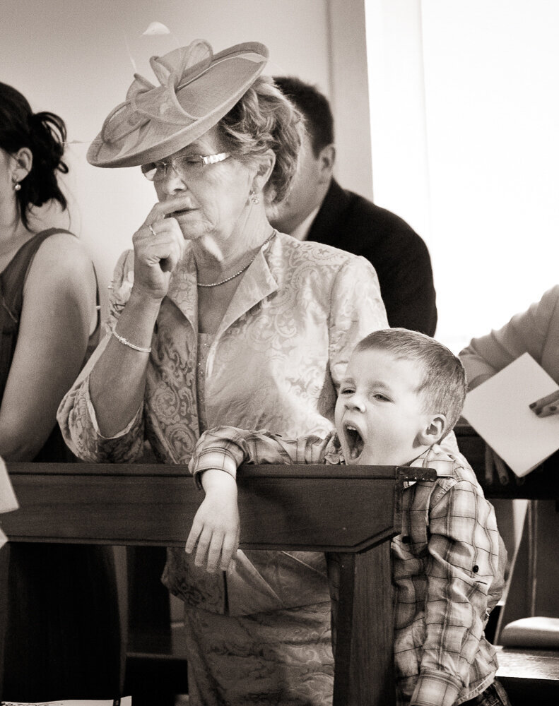 Mother of the bride wearing a fascinator hat sitting beside her grandson who is yawning in the church