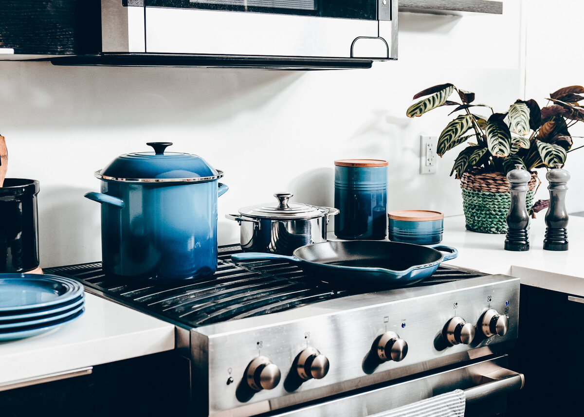A stainless steel range cooker is pictured with several ceramic blue pots on top.