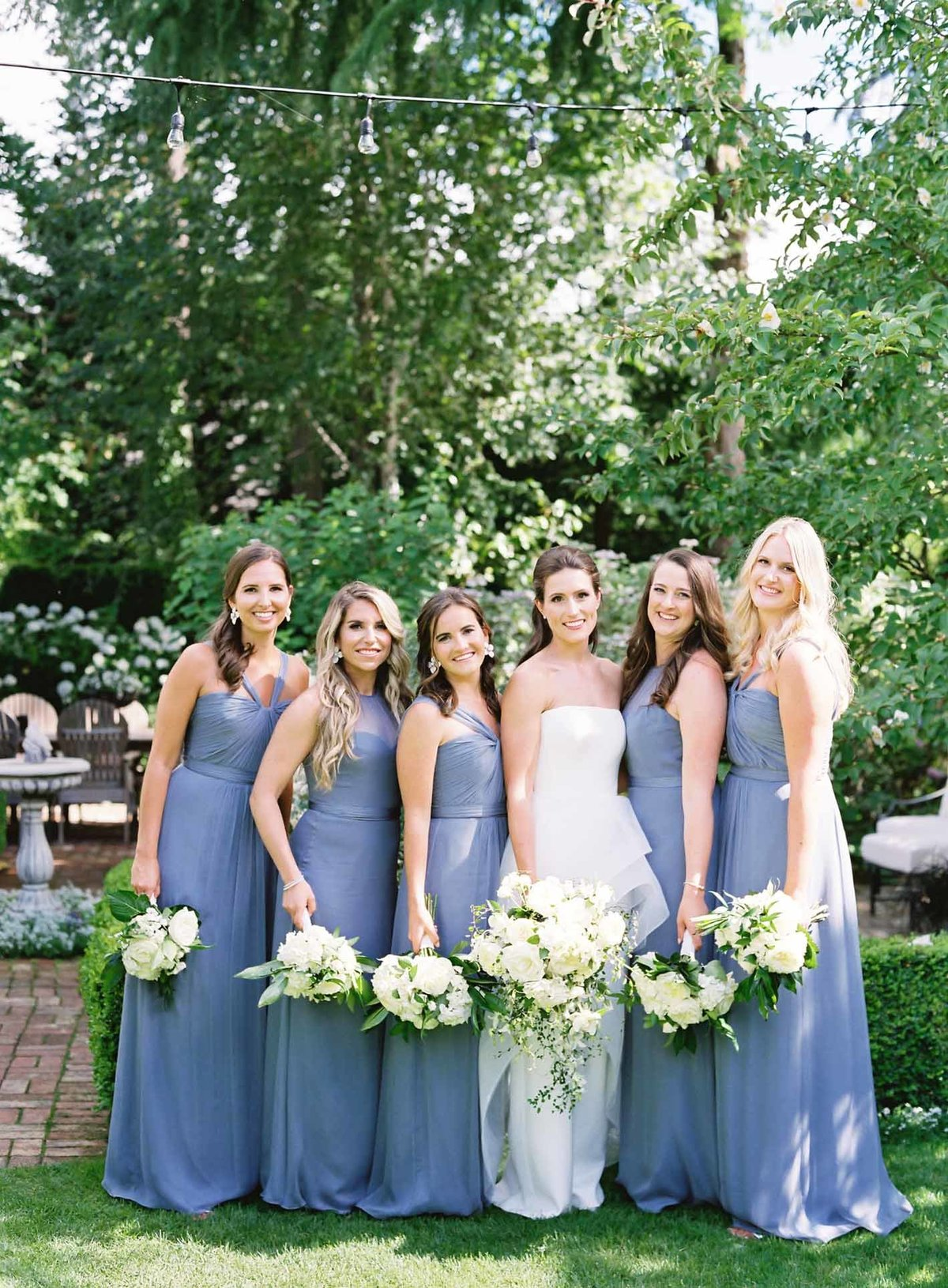 Kerry's bridesmaids all dressed in French blue gowns and holding white bouquets.