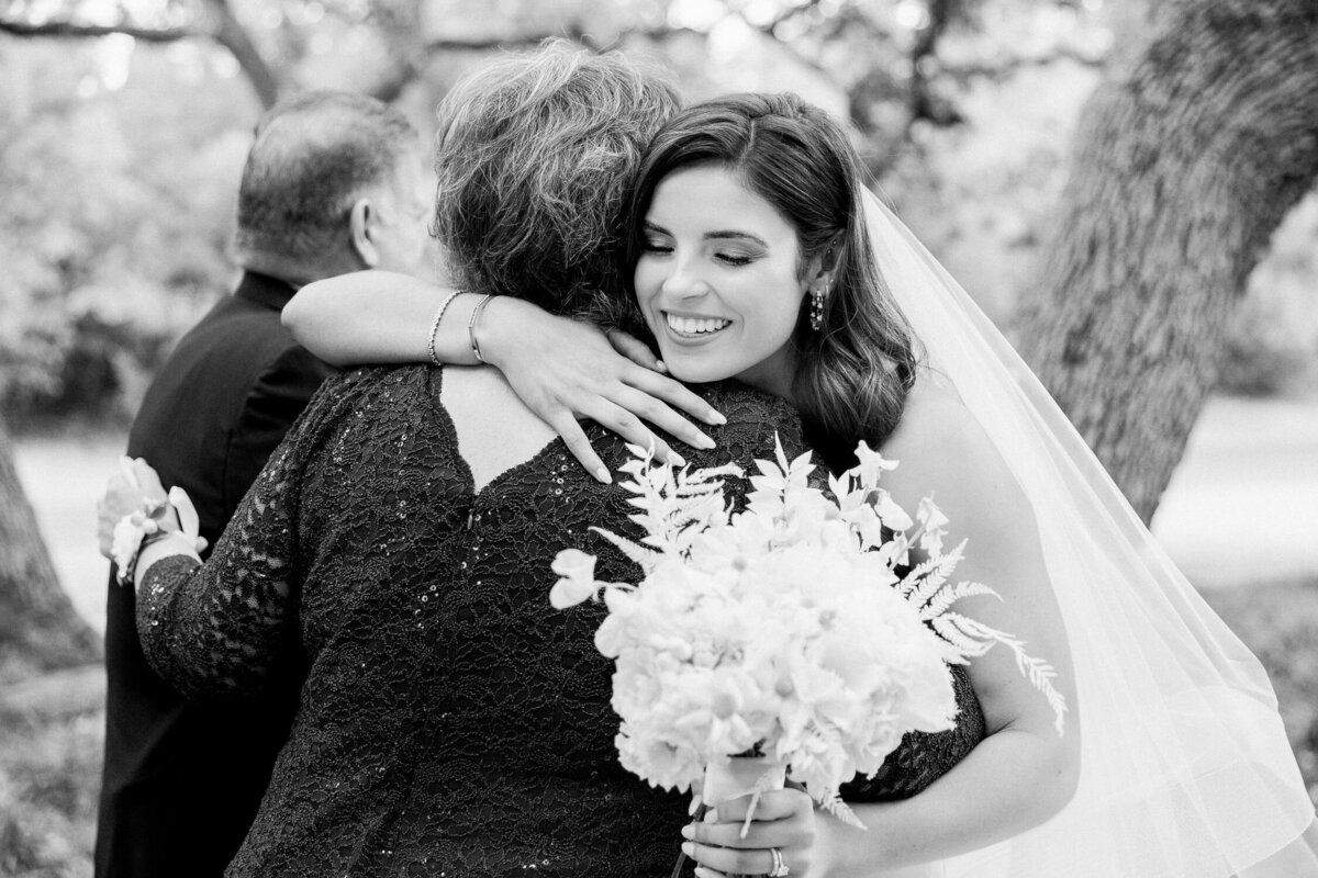 bride hugging mother and smiling on wedding day black and white