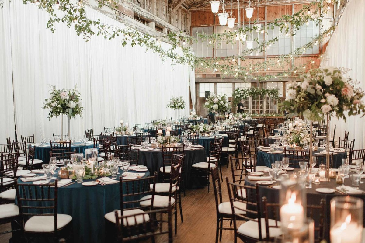 Wedding reception room photo with a mix of tall and low centerpieces.