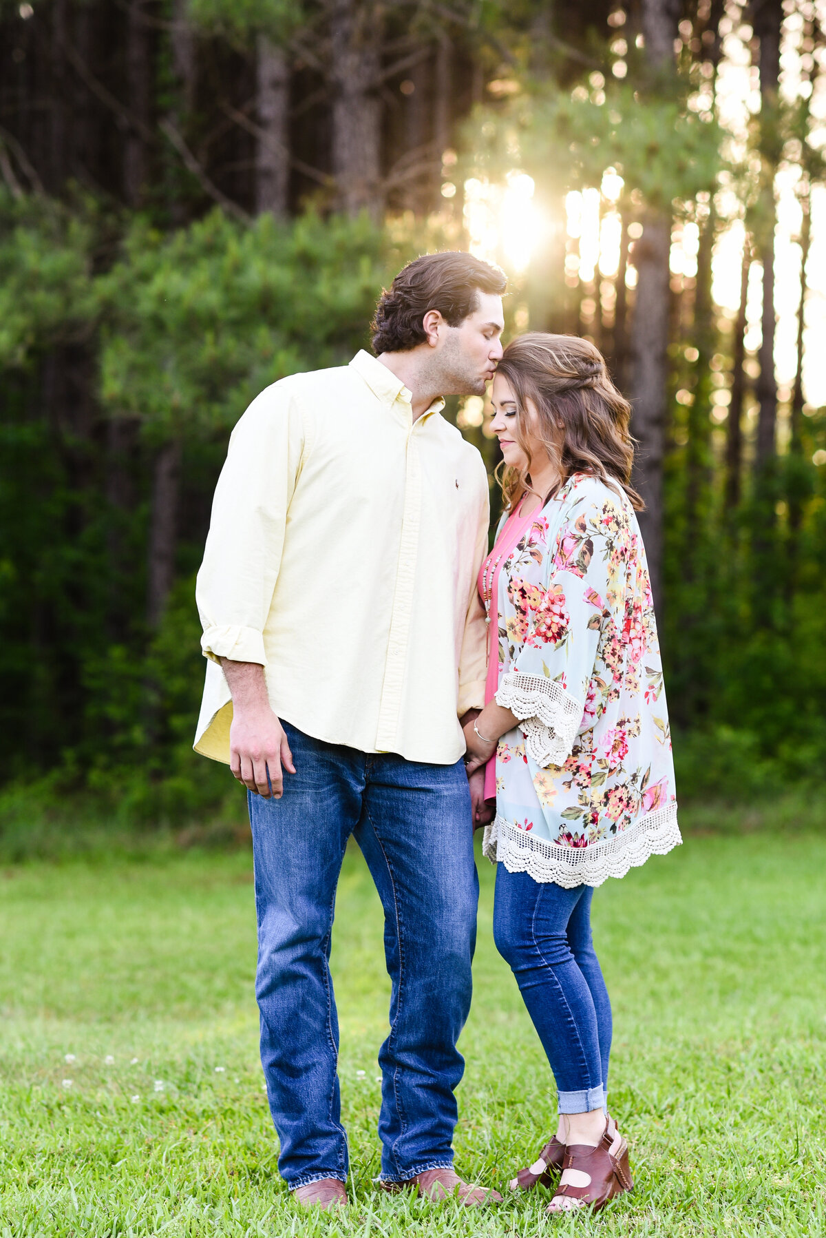 Beautiful Mississippi Engagement Photography: groom kisses bride in forest at sunset in Mississippi