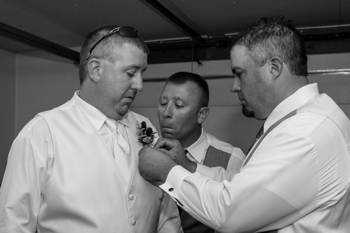 onlooking groomsman making funny face during getting dressed