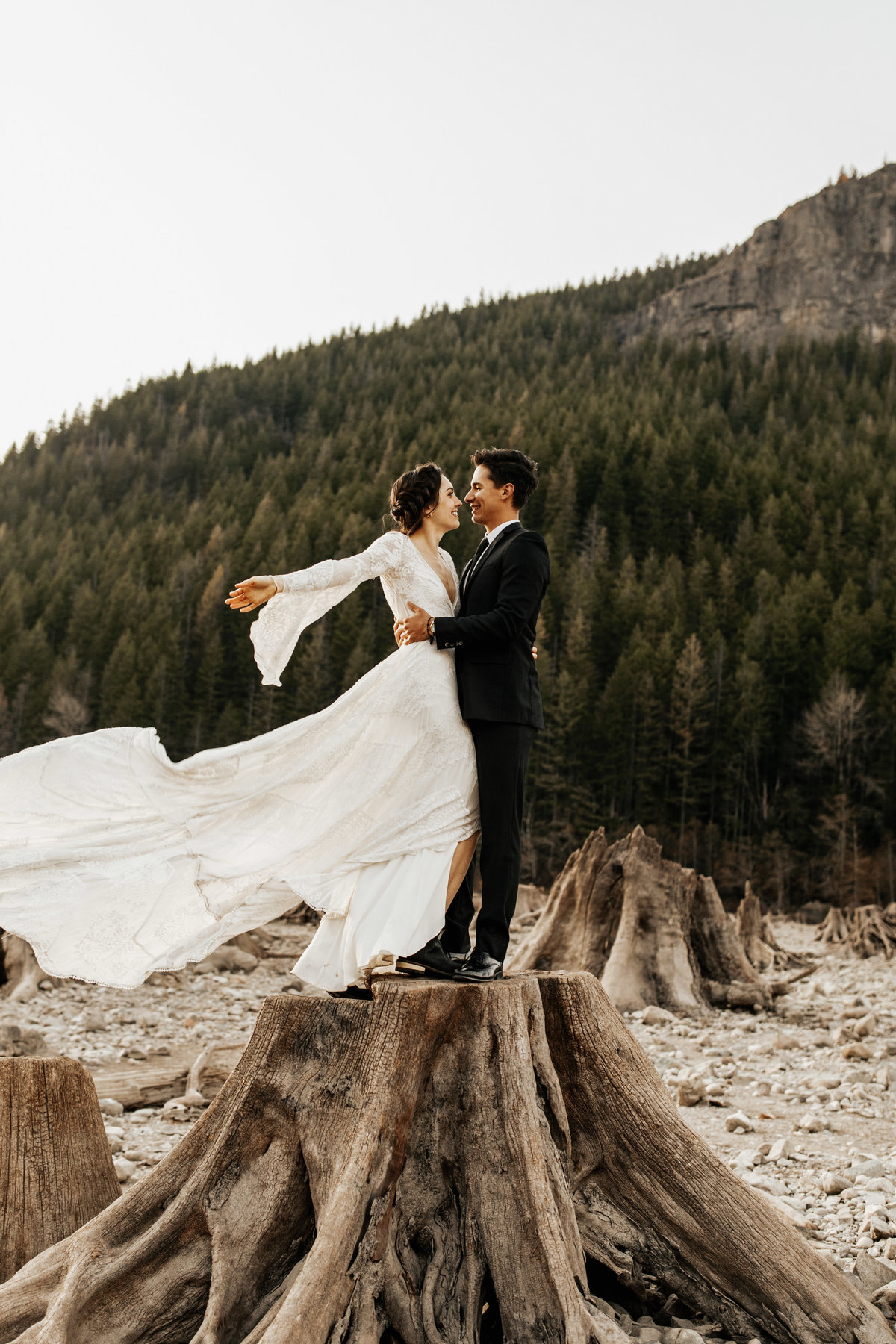 married couple standing on log kissing
