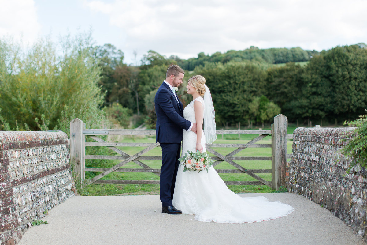 Beautiful natural light romantic landscape portrait of the bride and groom at Farbridge barn in West Dean on their wedding day