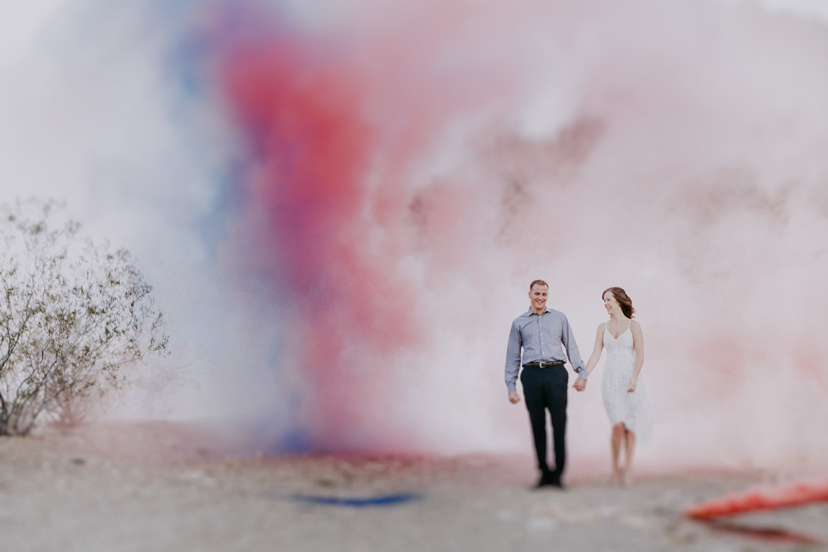 Lake Tahoe engagement pictures couple walks out of colorful smoke in desert
