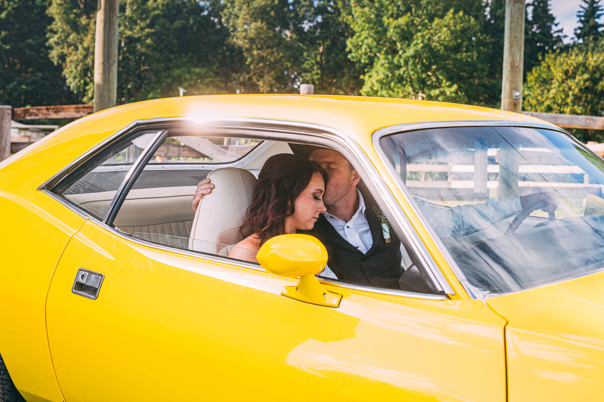 wedding photo of bride and groom in yellow sports car.