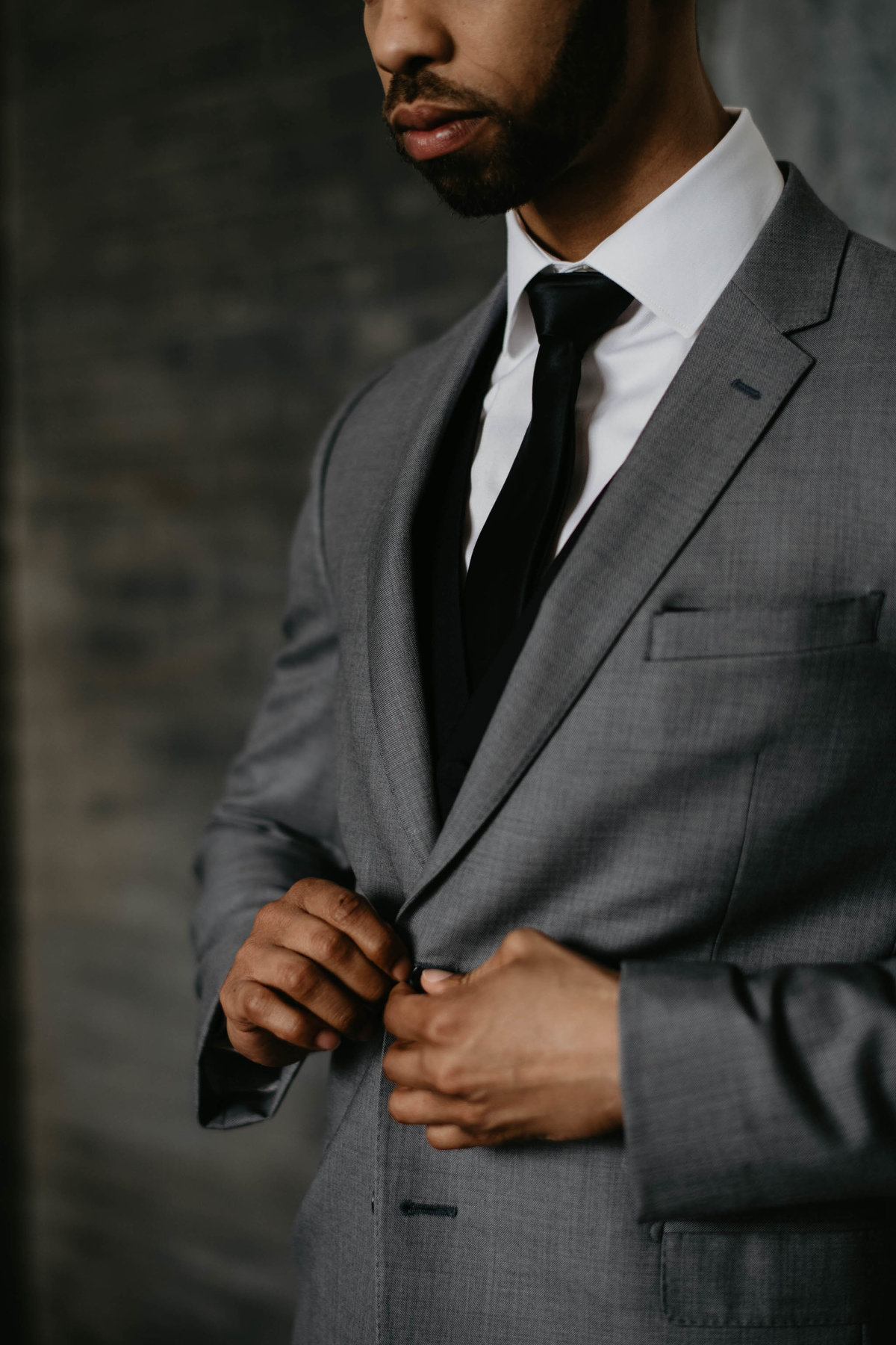 groom buttoning button on his suit