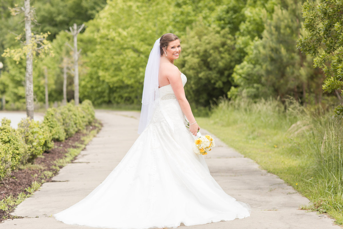 bride smiling with yellow flowers on a sunny day