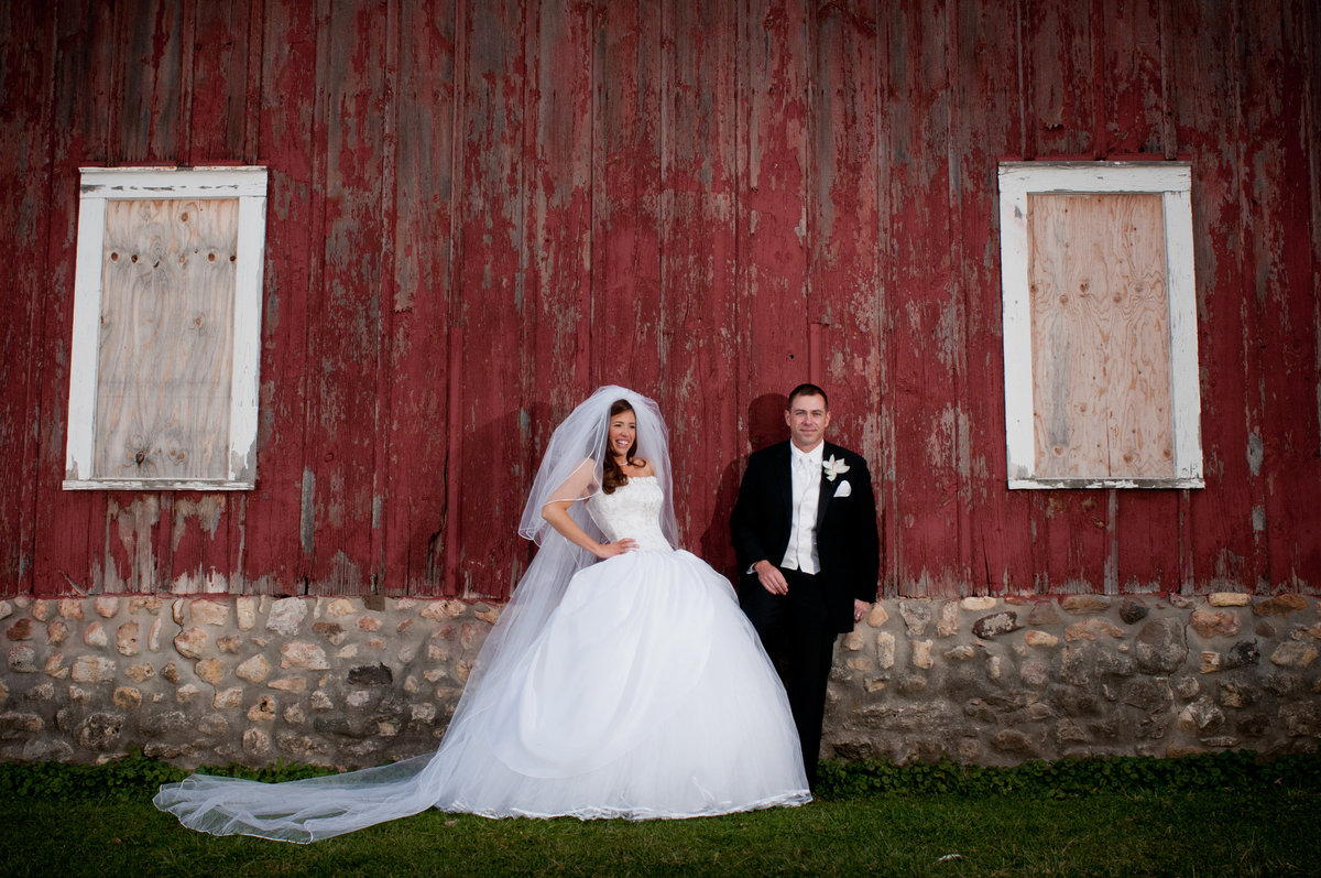A bride in a cinderella dress and groom pose for a portrait in front of a red barn