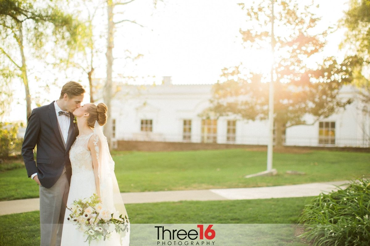 Bride and Groom stop to kiss during their photo shoot